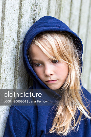 Portrait of sad blond girl wearing blue hooded jacket leaning against wooden wall - p300m2069964 by Jana Fernow