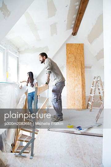 Couple in attic to be renovated looking out of window - p300m2083651 by Michelle Fraikin