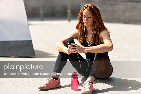 Sporty young woman with earphones having a break using smartphone outdoors - p300m2140665 by Javier Sánchez Mingorance