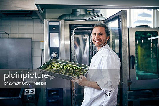 Portrait of confident chef with broccoli in baking sheet at commercial kitchen - p426m2016456 by Maskot