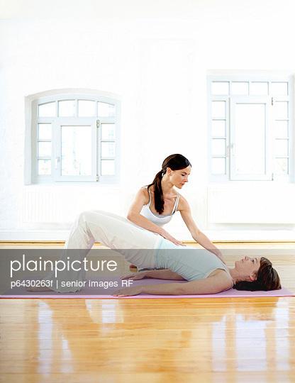 Pilatestrainerin zeigt Pilatesuebung  - p6430263f von senior images RF