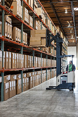 An employee picking products off a rack using a forklift stock picker in a distribution warehouse. - p1100m2002278 by Mint Images