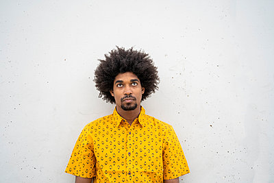 Young hipster wearing yellow shirt, looking up - p300m2131696 by VITTA GALLERY