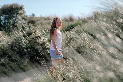 Girl standing in between of bush on sunny day - p300m2227053 by Oxana Guryanova