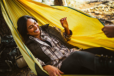 High angle view of smiling woman enjoying on hammock in forest during vacation - p426m2219073 by Maskot