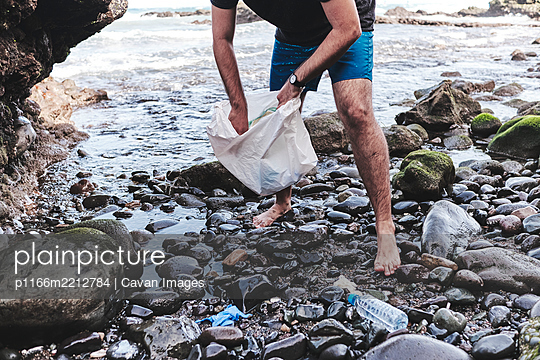 Anonymous Volunteer Cleaning Beach From Plastic - p1166m2212784 by Cavan Images