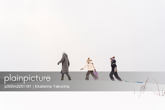 Father and children walking with sleds on snow covered land against sky - p300m2251181 by Ekaterina Yakunina