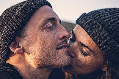 Kissing couple wearing wooly hats - p300m2083669 von Maya Claussen