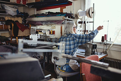 Senior owner using sewing machine at table in workshop - p426m1543002 by Maskot