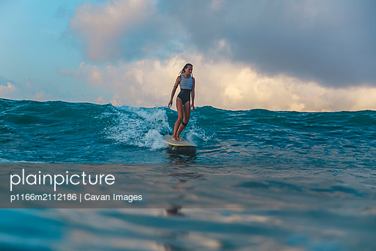 Female surfer on a wave - p1166m2112186 by Cavan Images