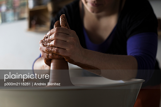 Potter forming clay on a wheel - p300m2118281 by Andrés Benitez