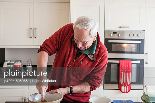 Senior male using wooden spoon in mixing bowl - p429m803068f by Hugh Whitaker