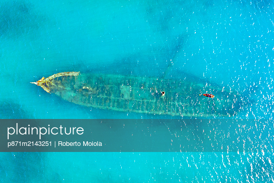 Aerial view by drone of a shipwreck in the shallow water of blue Caribbean Sea, Antilles, West Indies, Caribbean - p871m2143251 by Roberto Moiola