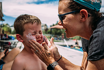 close up of mother putting sunscreen on boy's cheeks at pool - p1166m2182778 by Cavan Images
