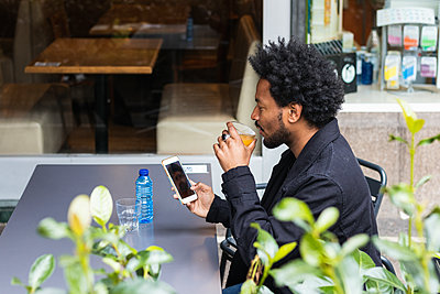 Man with afro hair having drink while using mobile phone at sidewalk cafe - p300m2244034 by NOVELLIMAGE