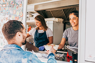 Smiling young female owner giving bowl of Tex-Mex to male customer from food truck - p426m2046482 by Maskot