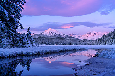 Alpenglow colours the snow-covered coastal range mountains, Mendenhall Glacier and Mendenhall towers are reflected in the open water along the edge of Auke Lake as the sun gets ready to set; Alaska, United States of America - p442m2074133 by John Hyde