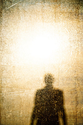 Silhouette of man with bright light above and textured screen - p597m2193080 by Tim Robinson