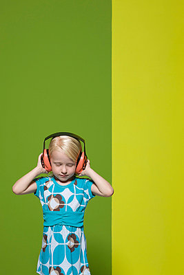 Little girl with eyes closed wearing protective headphones - p62314446f by Matthieu Spohn