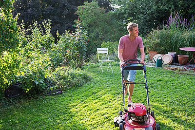 Young man lawn mowing - p825m1442101 by Andreas Baum