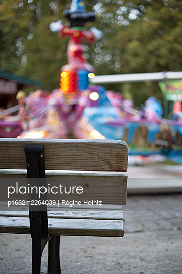 Bench in front of a carousel - p1682m2264039 by Régine Heintz
