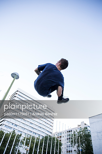 Spain, Madrid, man jumping in the city during a parkour session, low angle view