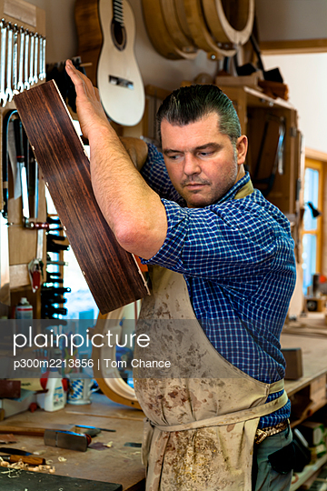Guitar maker in his workshop - p300m2213856 by Tom Chance