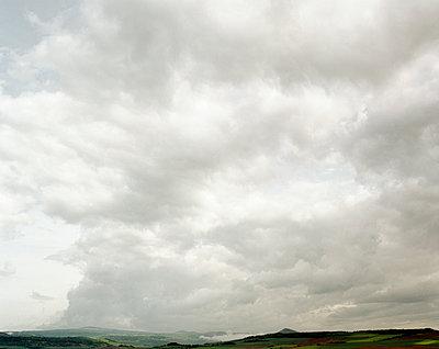 Bewölkter Himmel über Hügellandschaft - p1409m1464932 von margaret dearing