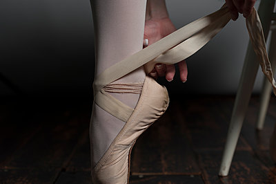 Female ballet dancer tying the ribbons on her pointe shoes. - p1433m1531936 by Wolf Kettler