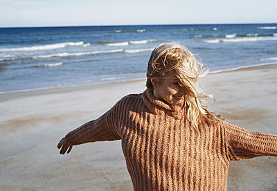 Happy woman having fun at the ocean beach - p1577m2150343 by zhenikeyev