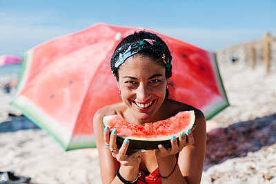 Close-up of smiling woman holding watermelon while sitting against red umbrella at beach - p300m2220808 by Ezequiel Giménez