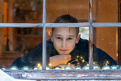 Boy with hand on chin looking through window while sitting at home during Christmas - p300m2256141 by Lisa und Wilfried Bahnmüller