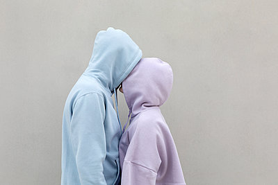 Couple in hooded shirt kissing by wall - p300m2276309 by Petra Stockhausen