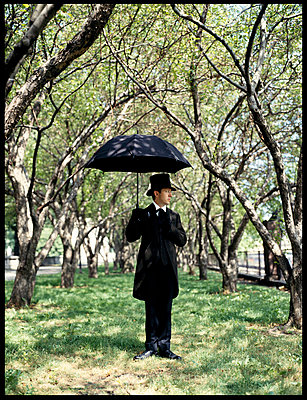 Man in coattails holds umbrella in park on sunny day - p3720188 by Tom Maday