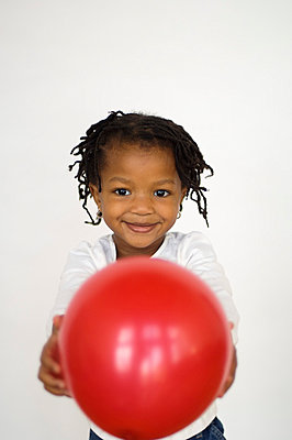 Portrait of young girl holding out balloon - p3720399 by James Godman