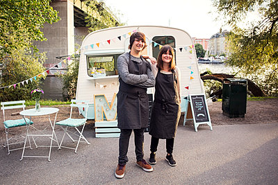 Full length portrait of confident owners standing on street against food truck - p426m1407061 by Maskot