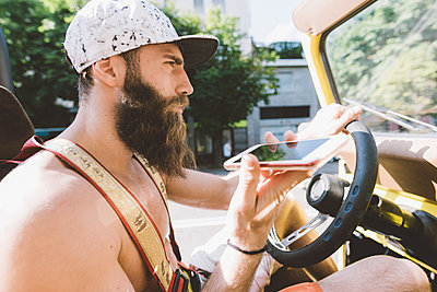 Young male hipster on road trip using smartphone navigation, Como, Lombardy, Italy - p429m1519479 by Eugenio Marongiu
