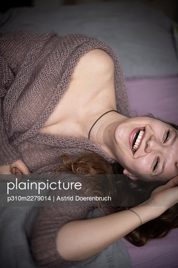 Laughing woman in bed - p310m2279014 by Astrid Doerenbruch