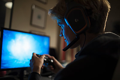 Teenage boy with headset playing video game at computer in dark room - p1023m2208322 by Sam Edwards