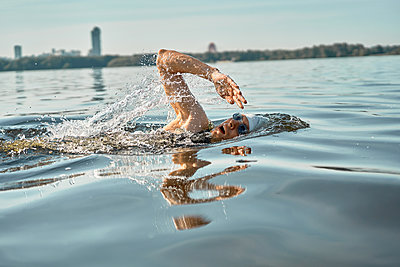 Young man in rubber cap swim on river on summer day. - p1630m2196907 by Sergey Mironov