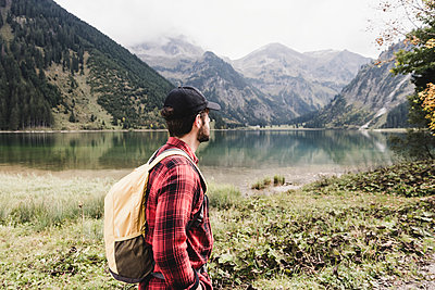 Austria, Tyrol, Alps, hiker standing at mountain lake - p300m1505209 by Uwe Umstätter
