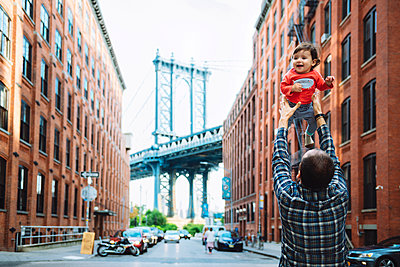USA, New York, New York City, Father playing with baby in Brooklyn with Manhattan Bridge in the background - p300m1587255 by Gemma Ferrando