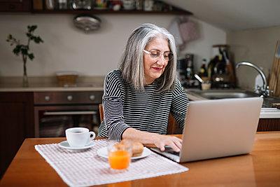 Portrait of senior woman using laptop at breakfast table - p300m2118903 von Alberto Bogo