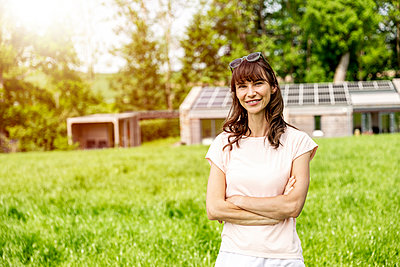 Portrait of smiling woman standing on meadow in front of a house - p300m2131861 by Jo Kirchherr