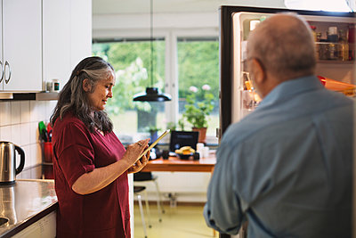 Side view of senior woman using digital tablet while man standing at refrigerator - p426m1131006f by Maskot