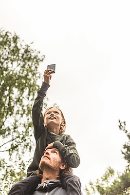 Low angle view of girl photographing through mobile phone while sitting on father's shoulders against sky - p426m2145652 by Maskot