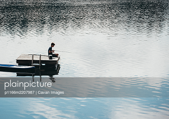 Teen boy fishing from a swim platform on a lake in the summer. - p1166m2207987 by Cavan Images