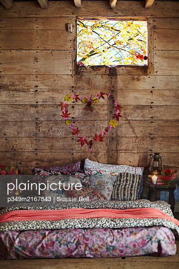 Assorted floral fabrics on mattress below heart of leaves and window in rustic wood cabin  Autumn  UK - p349m2167843 by Sussie Bell