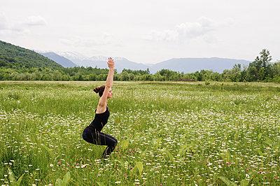 Girl practicing yoga on the mountain plain - p1412m2100833 by Svetlana Shemeleva