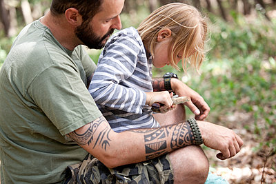 Father and daughter carving in the forest - p300m1499204 by Michelle Fraikin